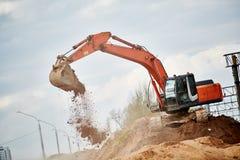 挖掘机装入程序在地球运动的工作 图库摄影