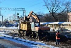 挖掘机装载击碎了石在翻斗车身体 铁路的建筑 地球的表面为放置做准备 图库摄影