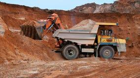 挖掘机装载的沙子到倾销者卡车里 履带牵引装置挖掘机工作 股票录像