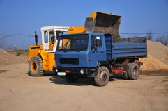 挖掘机装货土壤到倾销者卡车里 库存照片
