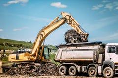 挖掘机装货在垃圾倾弃场的倾销者卡车 免版税图库摄影