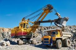 挖掘机装货花岗岩或矿石到翻斗车里在露天开采 库存照片