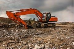 挖掘机运动的地球和石头在路的建筑工作 免版税库存图片
