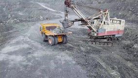 挖掘机顶视图在露天开采矿的 挖掘机睡着在倾销者的瓦砾在矿物的提取的室外猎物 股票视频