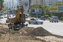 挖掘机,扩展路的工作在Pyatigorsk,俄罗斯 免版税库存照片