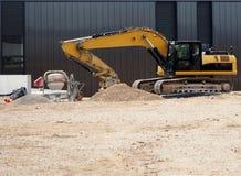 挖掘机,水泥搅拌车,一辆独轮车肩并肩在有后边一个新的黑大厦的一个建造场所 库存照片
