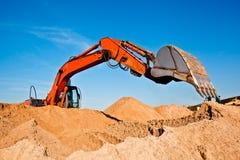 挖掘沙子的开掘的挖掘机 图库摄影
