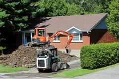 挖掘郊区家的建筑器材 免版税库存照片