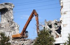 挖泥机毁坏一个老大厦 免版税库存照片