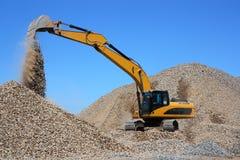 挖泥机装载瓦砾 免版税库存照片