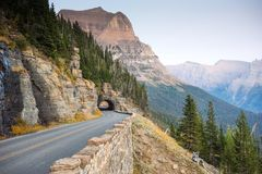 挖洞的山路在路对太阳在冰川国家公园 免版税库存图片