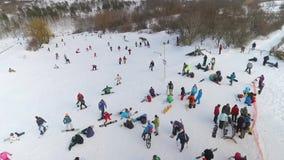 挡雪板、滑雪者和山骑自行车的人天线有休息在倾斜顶部 股票录像