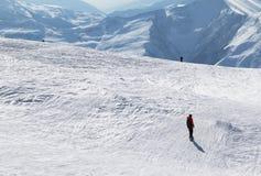 挡雪板和滑雪者下坡多雪的倾斜的 库存照片