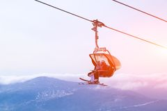 挡雪板和滑雪者专业成套装备的爬上电车推力山在天空、太阳和山峰背景  免版税库存图片