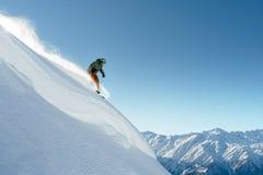 挡雪板在一个美好的风景的陡峭的山腰乘坐 免版税库存图片
