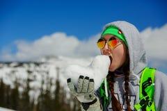 年轻挡雪板女孩画象有雪心脏的在手上 免版税库存照片