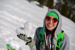 年轻挡雪板女孩画象有雪心脏的在手上 免版税图库摄影