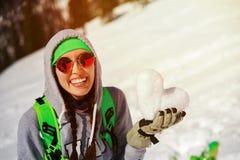 年轻挡雪板女孩画象有雪心脏的在手上 图库摄影