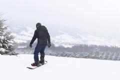 挡雪板障碍滑雪下来在积雪覆盖的山背景  冬季体育的现代运动器材 山区度假村 免版税库存图片