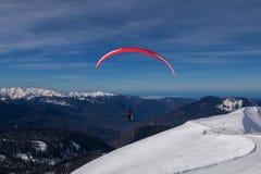 挡雪板,行动的滑雪者在山 有辅导员的滑翔伞 免版税库存照片