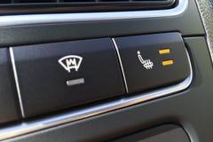 挡风玻璃加热器和位子热化的按钮在一个现代汽车特写镜头 免版税库存照片