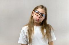 挣扎她的面孔的玻璃的滑稽的白肤金发的女孩,仿造,获得乐趣 r 免版税库存图片