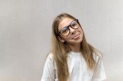 挣扎她的面孔的玻璃的滑稽的白肤金发的女孩,仿造,获得乐趣 r 免版税库存照片