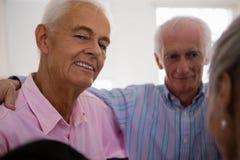 挤作一团与朋友的老人画象 免版税库存图片