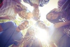 挤作一团在圈子的愉快的朋友在公园 免版税库存照片