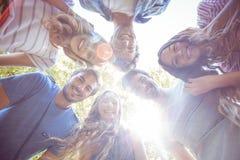 挤作一团在圈子的愉快的朋友在公园 免版税库存图片