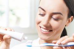 挤在牙刷上的妇女牙膏在卫生间 库存照片