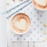 挤奶与心脏的茶由桂香制成在白色木背景 库存照片