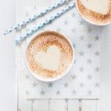 挤奶与心脏的茶由桂香制成在白色木背景 免版税库存照片