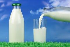 挤奶倾吐从瓶入玻璃 图库摄影
