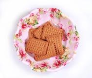 挤奶在一块被设计的五颜六色的食物板材的饼干 免版税库存照片
