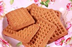 挤奶在一块被设计的五颜六色的食物板材的饼干 免版税库存图片