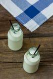 挤奶在木背景的一个瓶 库存照片