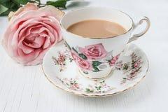 挤奶在瓷茶杯的茶,有桃红色玫瑰的 库存照片