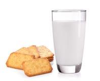 挤奶在玻璃和薄脆饼干在白色背景 免版税库存照片