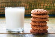 挤奶在玻璃杯子用在木桌上的麦甜饼 库存照片