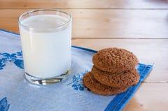 挤奶在玻璃杯子用在木桌上的麦甜饼 图库摄影
