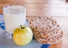 挤奶在玻璃杯子用苹果,在木桌上的薄脆饼干 库存图片