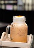 挤奶在玻璃杯子的泰国茶在木桌上 免版税库存照片