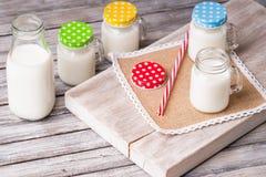 挤奶有五颜六色的盖帽的瓶子在切板和吸管 免版税库存照片