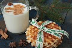 挤奶用在一个透明杯子的桂香,奶蛋烘饼,蛋糕,栓与圣诞节丝带,茴香 免版税库存照片