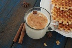 挤奶用在一个透明杯子的桂香,奶蛋烘饼,蛋糕,栓与圣诞节丝带,茴香 库存图片