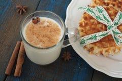 挤奶用在一个透明杯子的桂香,奶蛋烘饼,蛋糕,栓与圣诞节丝带, 免版税库存图片