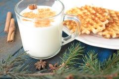 挤奶用在一个透明杯子的桂香,奶蛋烘饼,蛋糕,栓与圣诞节丝带, 库存图片