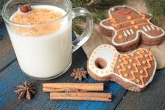 挤奶用在一个透明杯子的桂香,奶蛋烘饼,蛋糕,栓与圣诞节丝带, 免版税图库摄影