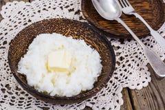 挤奶米粥用在木碗的黄油 库存图片